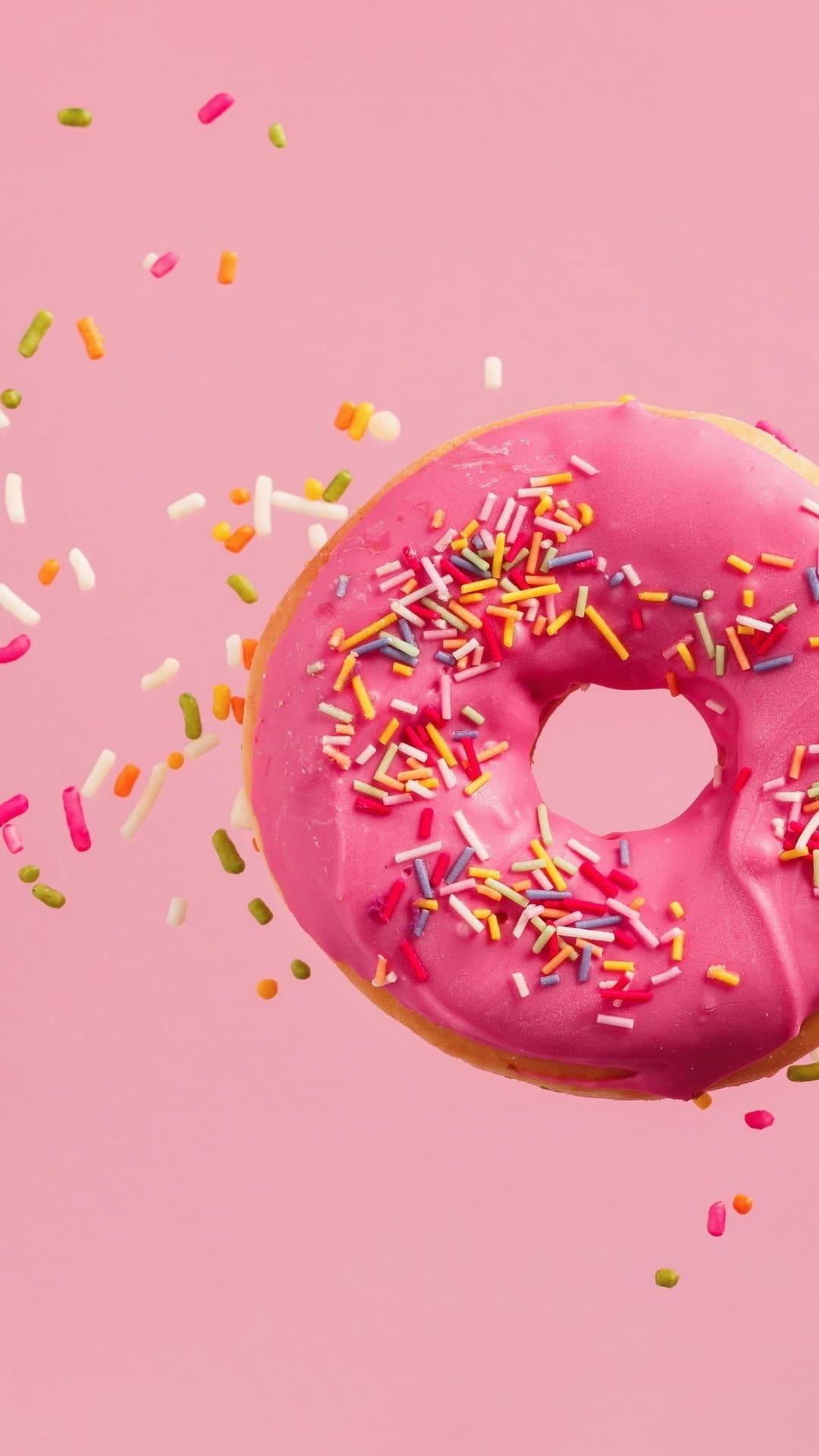 Roze donut met gekleurde sprinkles erop en errond